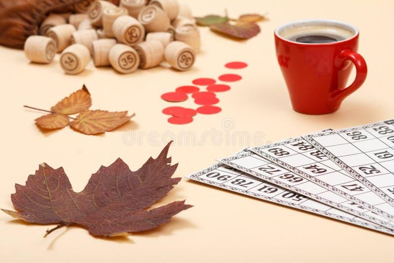 与袋子、游戏卡、干燥叶子和苹果的木乐透纸牌桶在米黄背景 库存图片