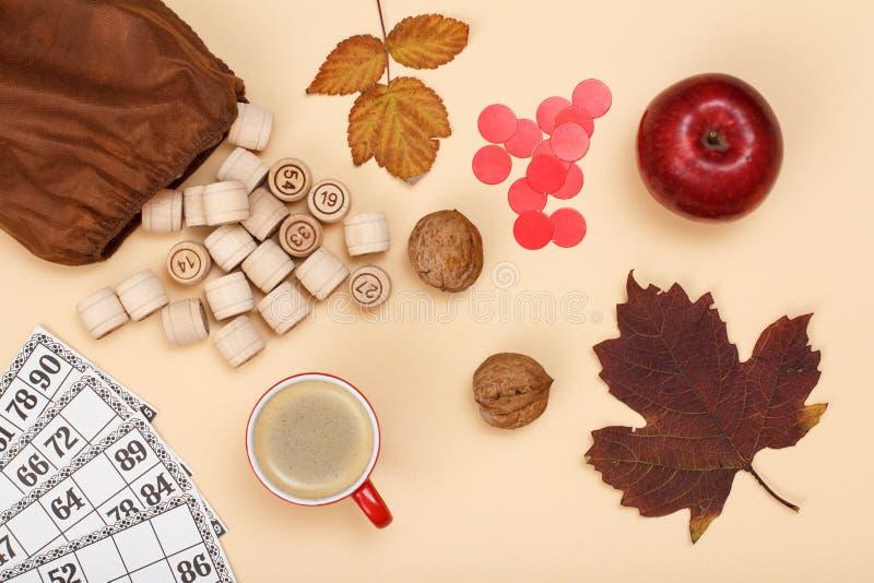 与袋子、游戏卡、苹果和咖啡的木乐透纸牌桶在米黄背景的 秋天题材 免版税库存照片