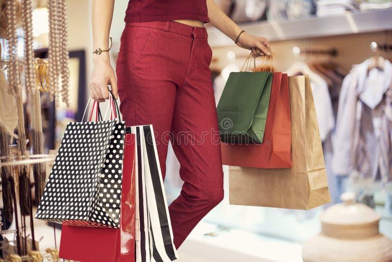 与袋子的妇女购物在精品店 免版税库存图片