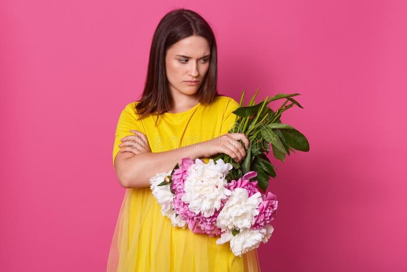 与被交叉的双臂的生气失望的年轻女人身分,在一只手上拿着花,看在旁边,有令人不快的脸面护理 库存图片