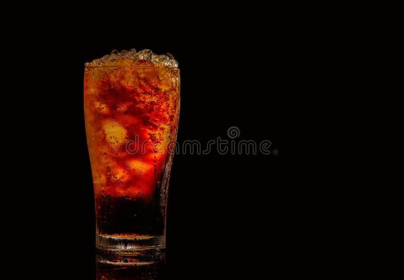 与被击碎的冰块的软饮料在与拷贝空间的黑暗的背景隔绝的玻璃 有水滴在玻璃的 图库摄影