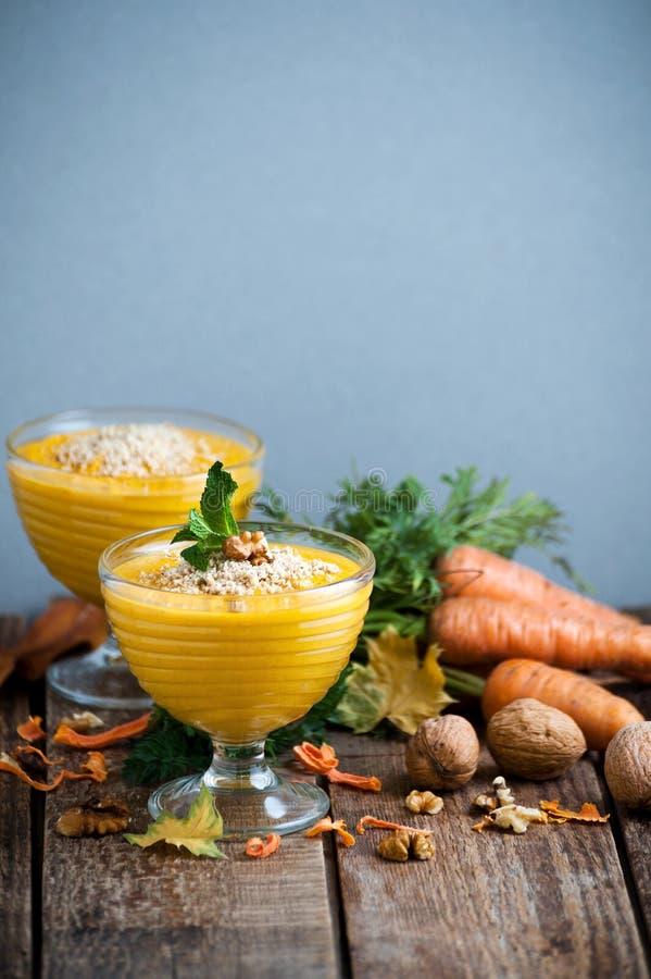 与被击碎的坚果的胡萝卜布丁在玻璃碗供食 免版税库存照片