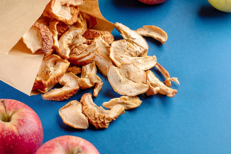 与被分散的干苹果切片和整个果子的纸袋在蓝色背景 库存照片