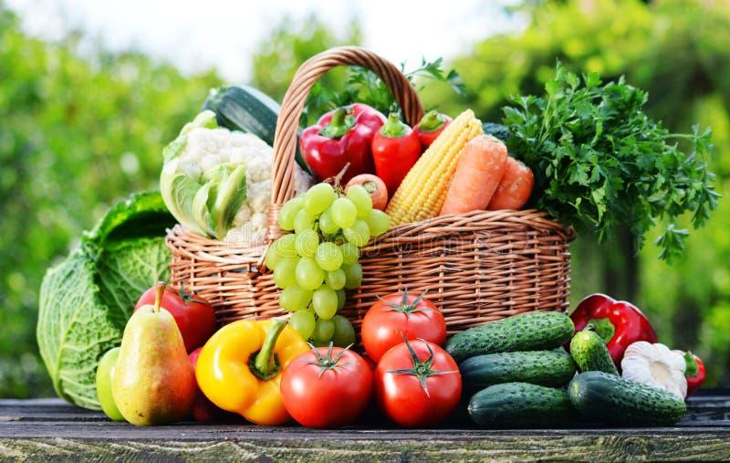 与被分类的未加工的有机菜的柳条筐在庭院里 免版税库存照片