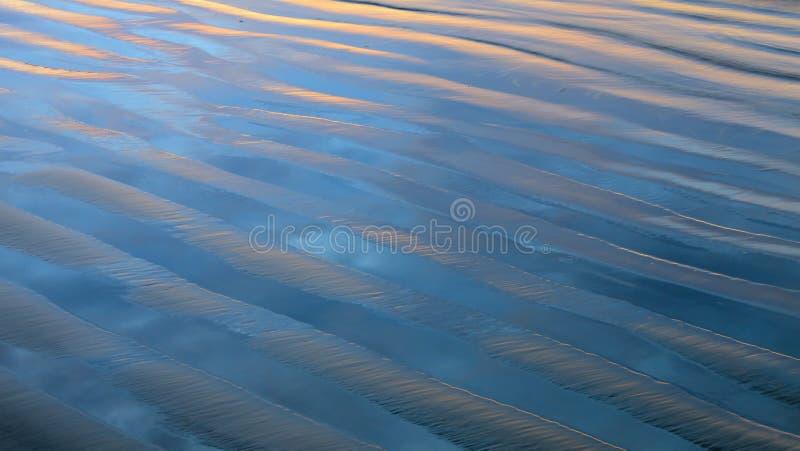 与被反射的日落颜色的波浪沙子纹理 免版税库存照片