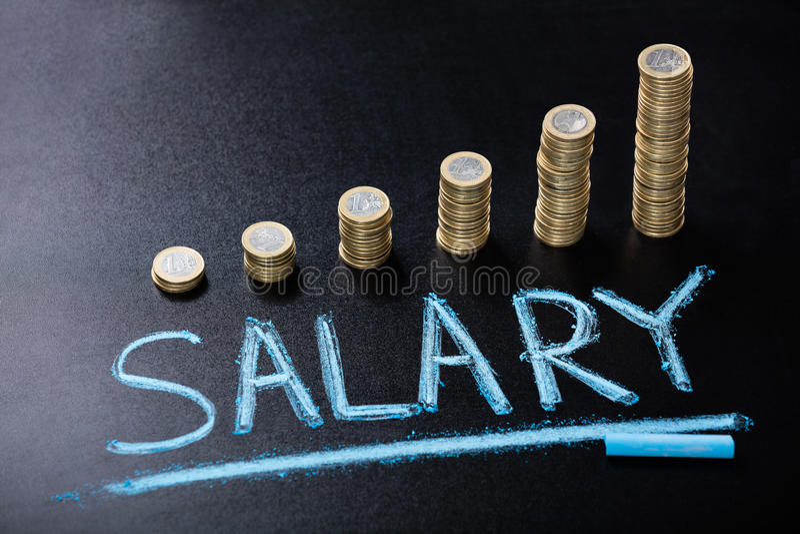 与被堆积的硬币的薪金概念在黑板 免版税库存照片