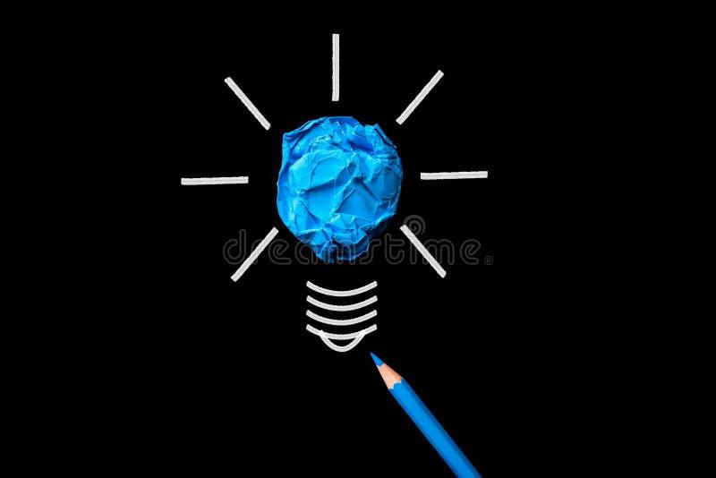 与被弄皱的五颜六色的纸的电灯泡和在黑背景否决 免版税库存照片