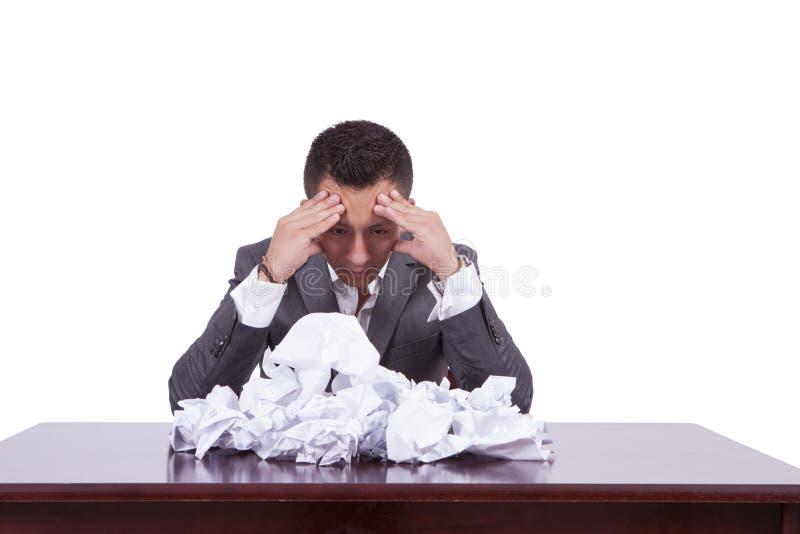 与被弄皱的纸的被拉紧的年轻商人在他的书桌上 免版税库存照片
