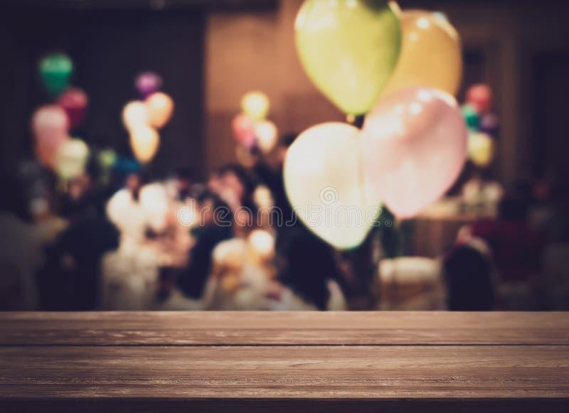 与被弄脏的人的空的木柜台在有五颜六色的气球的宴会房间 图库摄影