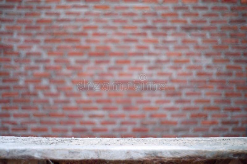 与被弄脏的砖砌墙壁的空的多灰尘的肮脏的木桌在背景中 免版税库存照片