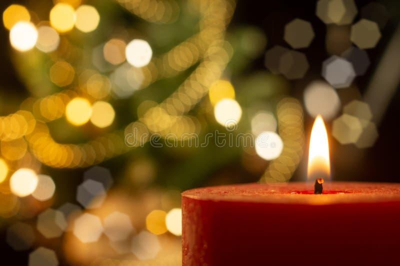 与被弄脏的Xmas树的被点燃的蜡烛在背景 免版税库存图片