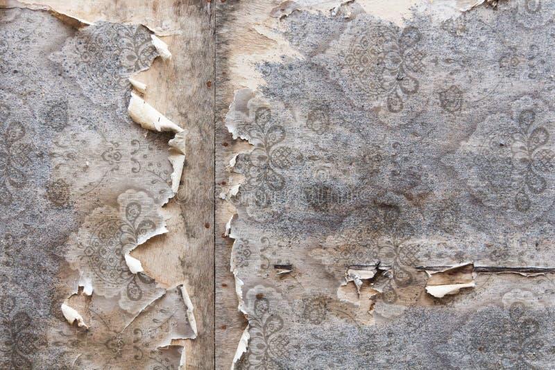 与被撕毁的葡萄酒墙纸的年迈的室墙壁背景 库存照片