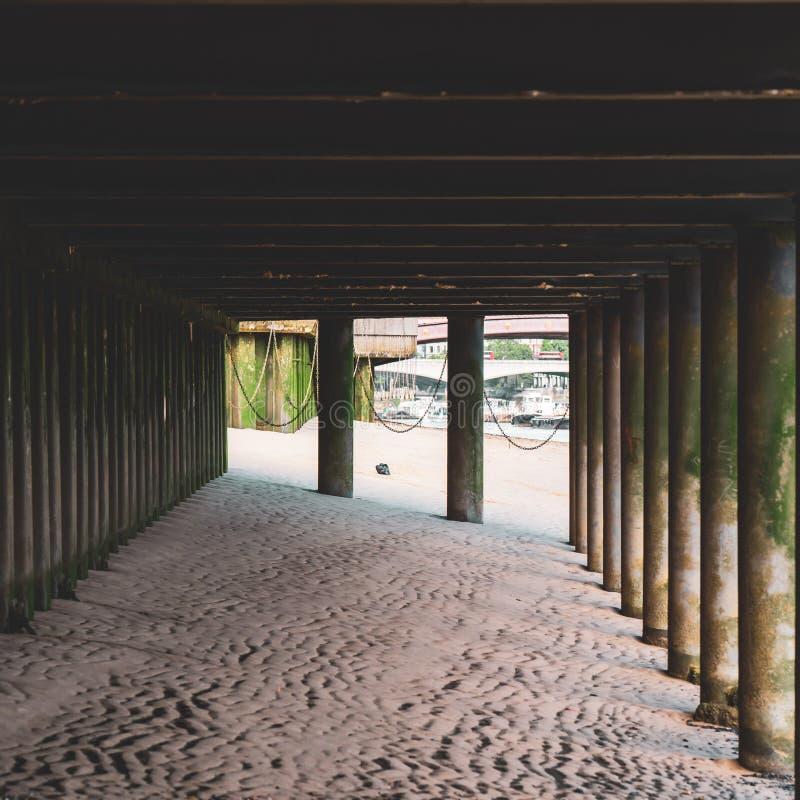 与被暴露的柱子和一个唯一乱丢沙子银行的垃圾袋子的泰晤士河沿低潮 免版税库存图片