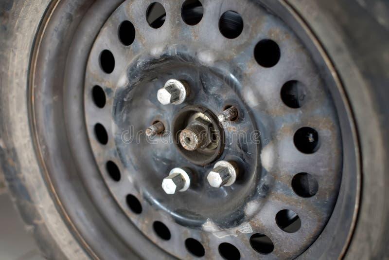 与被松开的螺栓的老生锈的车轮盘 库存图片