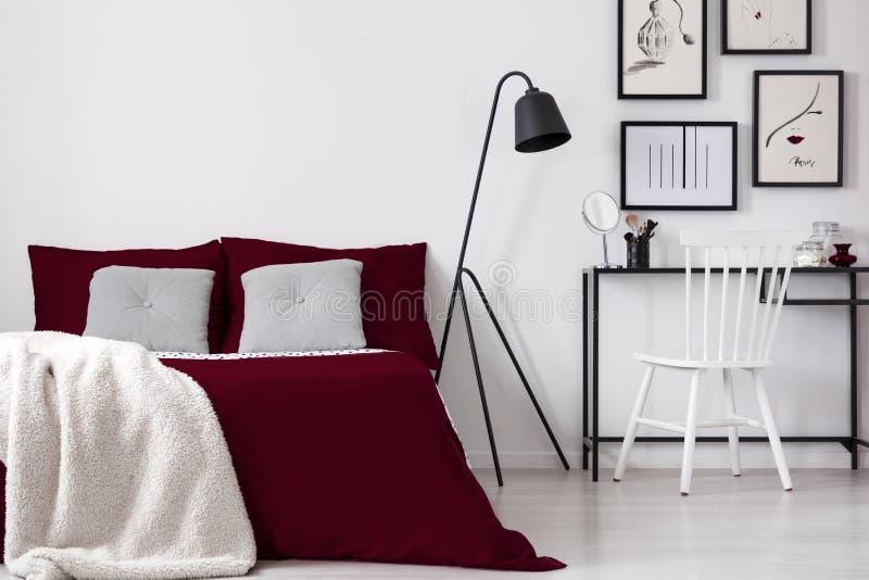 与被构筑的图画的少年` s艺术性的卧室内部在构成桌和一张舒适的床上在伯根地亚麻布a穿戴了 免版税图库摄影