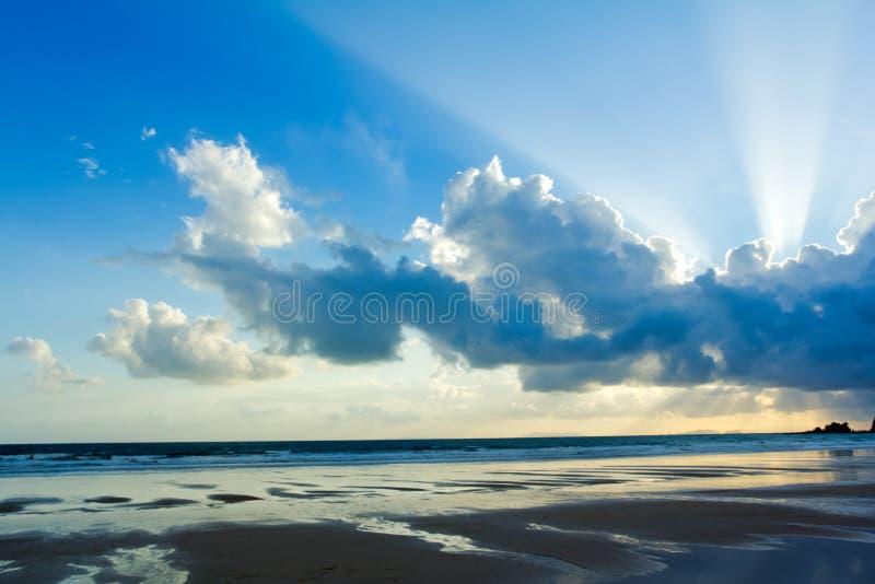 与被点燃的云彩的热带海滩日落天空 免版税库存图片