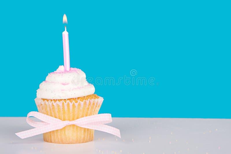 与被点燃的桃红色蜡烛的唯一杯形蛋糕 库存图片