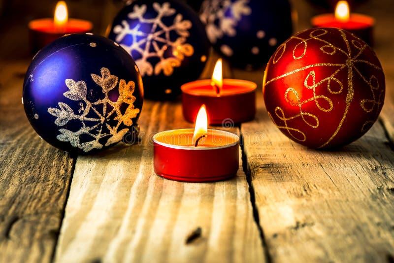 与被点燃的蜡烛的圣诞节蓝色和红色球在困厄的木背景 免版税库存图片
