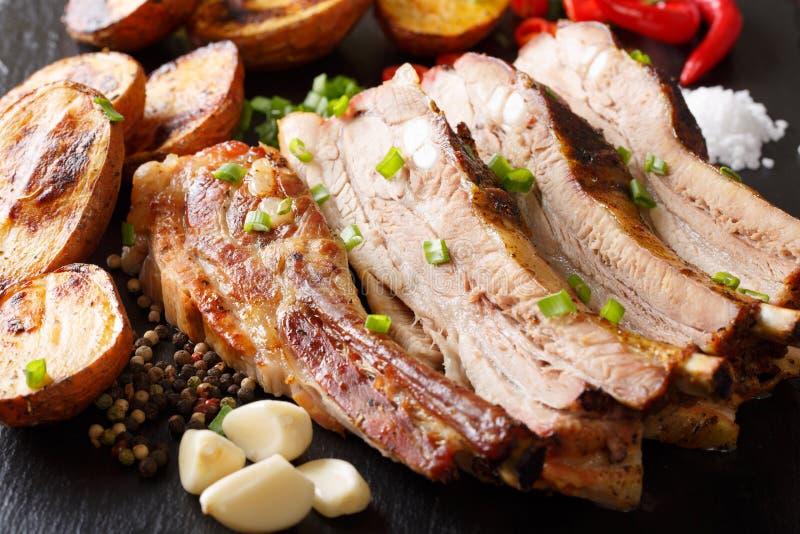 与被烘烤的土豆特写镜头的油煎的自创猪肉胸肉在ta 图库摄影