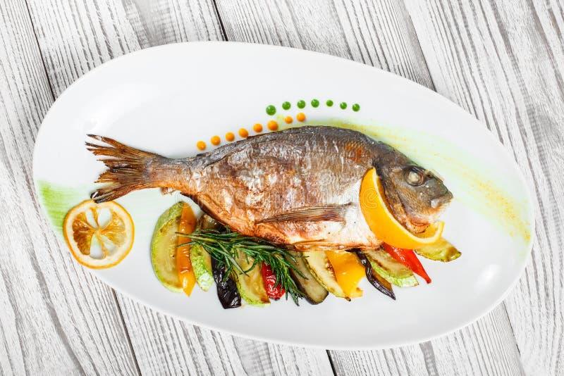 与被烘烤的菜和迷迭香的烤dorado鱼在木背景关闭的板材 免版税库存照片