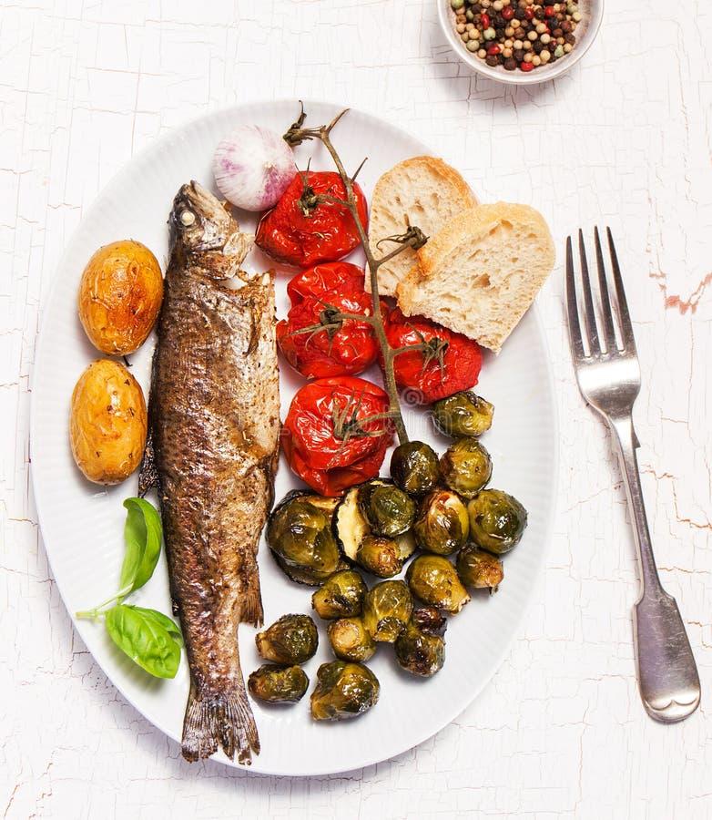 与被烘烤的菜和面包的自创被充塞的和烤鱼 免版税库存照片