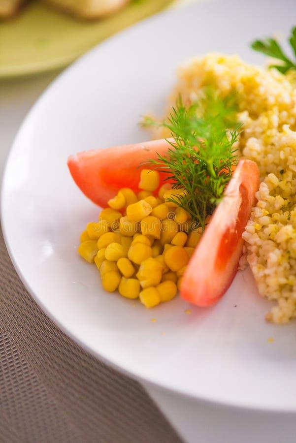与被烘烤的鱼菜和卷的碾碎干小麦用玉米、蕃茄和柠檬在一块白色板材 图库摄影
