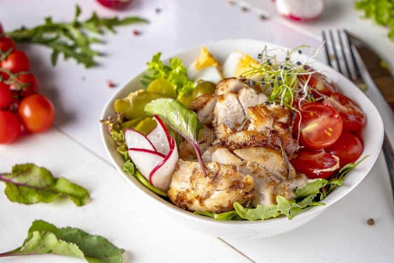 与被烘烤的鸡、奎奴亚藜、西红柿、萝卜、鸡蛋、腌汁黄瓜、microgreens和芝麻菜的健康菩萨碗午餐 库存图片