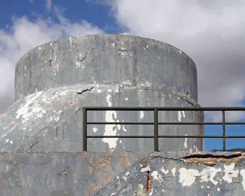 与被环绕的无窗的表面和绿色栏杆的一个老粉碎的具体军事地堡类型结构反对蓝色 库存照片