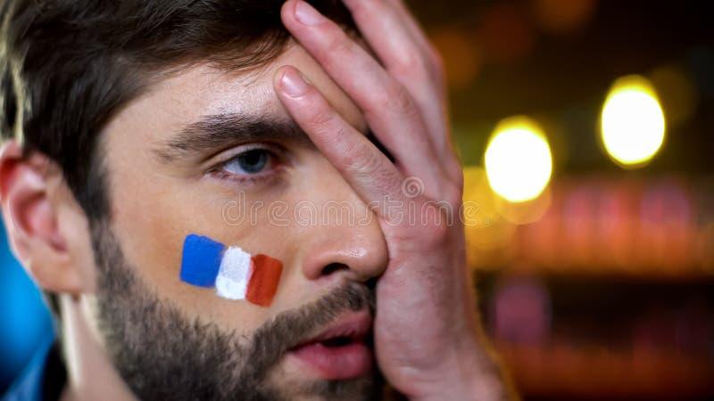 与被绘的旗子的急切法国爱好者在做facepalm,失望的面颊 免版税库存图片