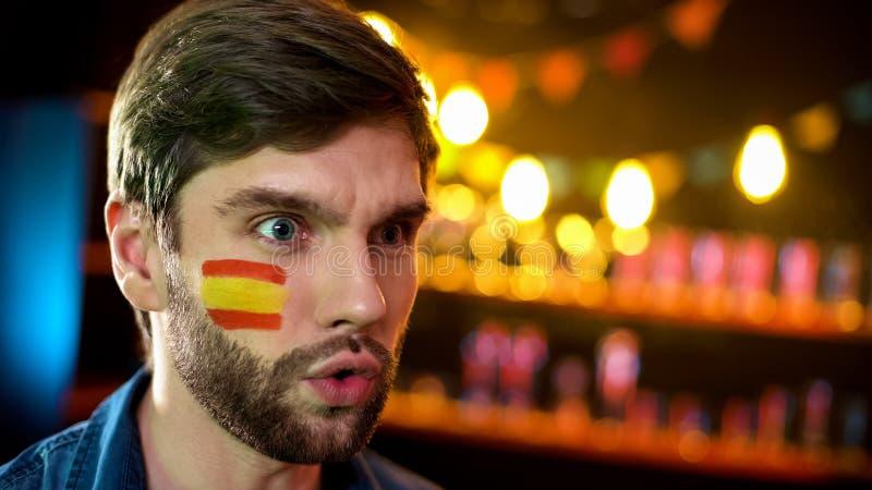 与被绘的旗子的震惊西班牙爱好者在对比赛不满意的面颊 库存照片