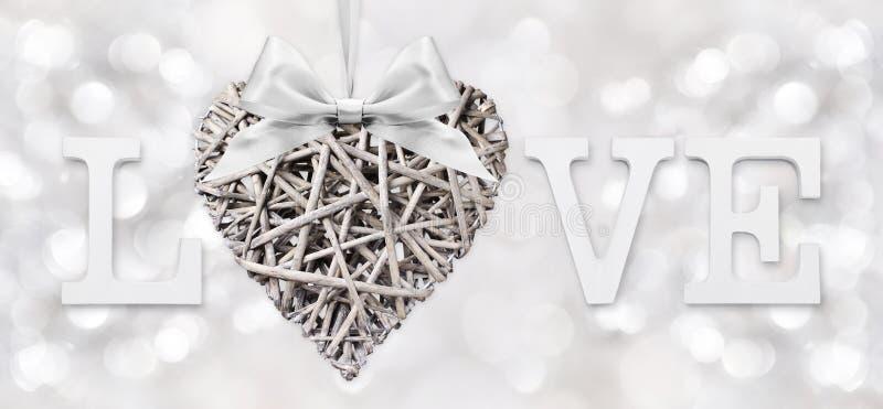 与被编织的木头的心脏的爱文本与丝带弓的在银 免版税库存图片