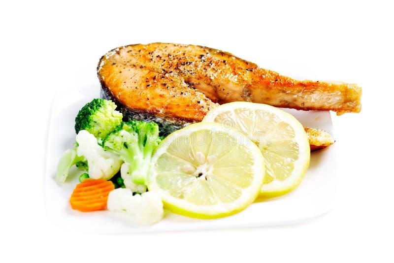 与被蒸的菜的烤三文鱼在丝毫隔绝的板材 免版税库存图片