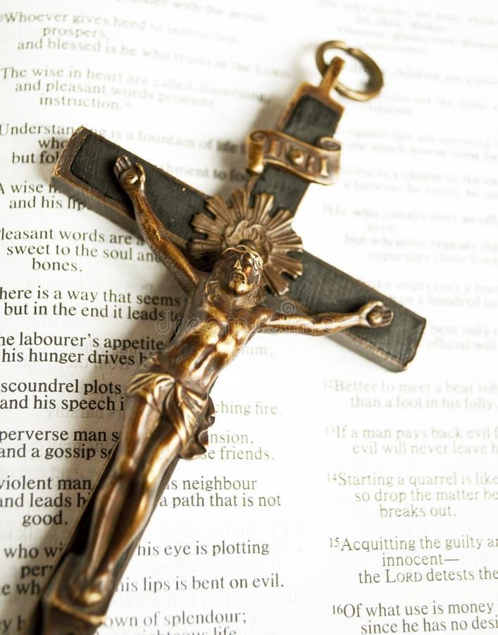 与被迫害的耶稣基督的十字架开放圣经的 免版税图库摄影