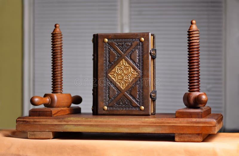 与被镀金的主题的古色古香的皮革书经受葡萄酒木装订新闻 免版税库存照片