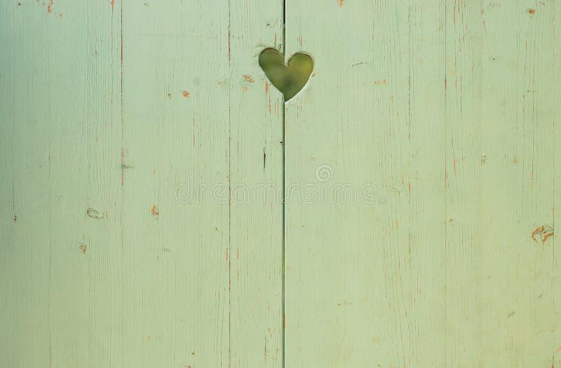 与被雕刻的心形的爱背景在绿色木委员会 库存图片