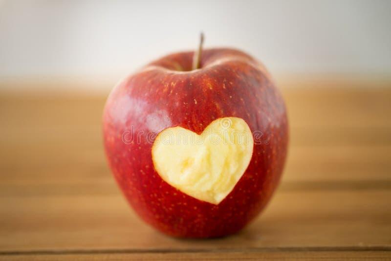 与被雕刻的心形的红色苹果在木桌上 库存照片