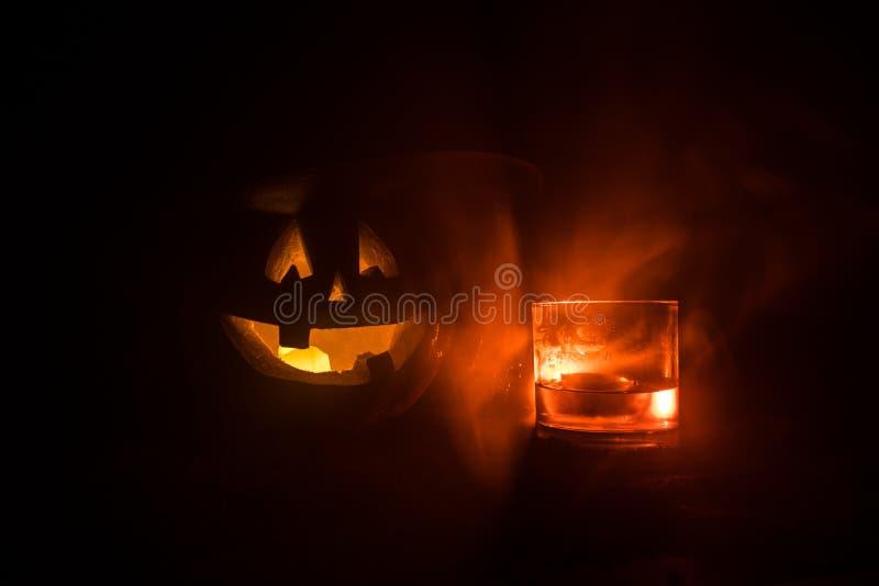 与被雕刻的面孔的万圣节南瓜和杯与冰的威士忌酒在与蛇神的黑暗的被定调子的有雾的背景 ?? 免版税库存图片