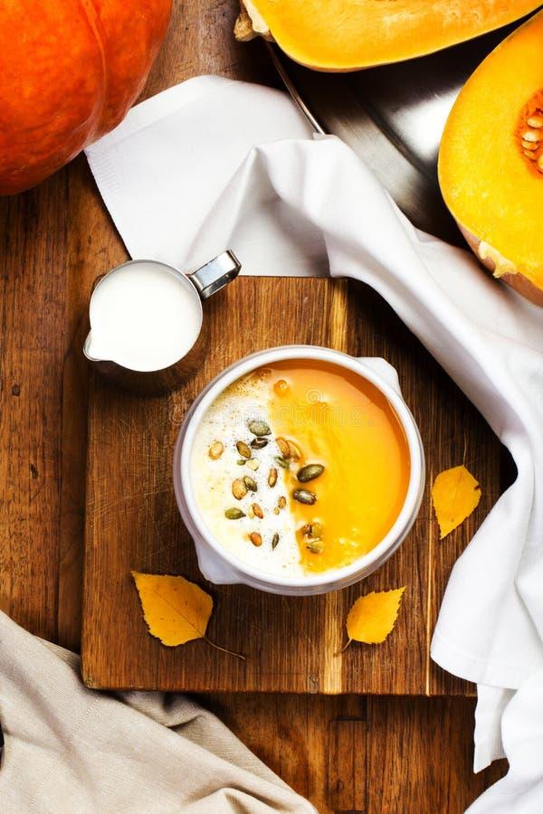 与被鞭打的奶油和南瓜籽的南瓜汤在白色pla 免版税库存照片