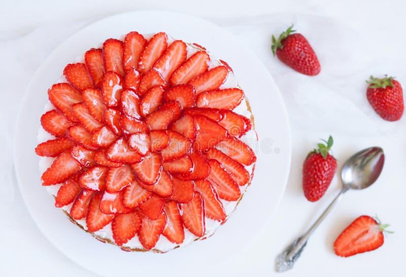 与被鞭打的奶油色顶部的自创维多利亚点心夹心蛋糕,装饰用草莓 关闭在桌上 免版税库存照片