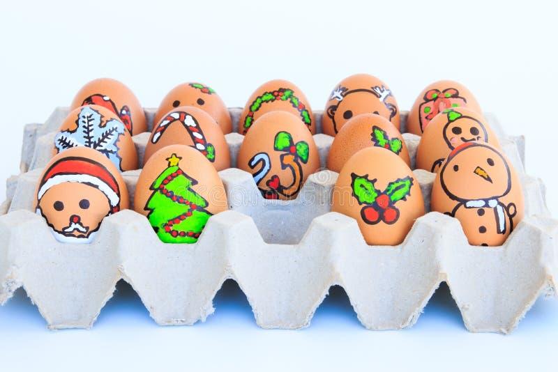 与被画的面孔的圣诞节鸡蛋在纸盒安排了 免版税库存照片