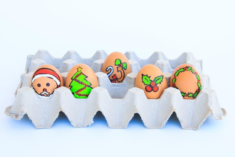 与被画的面孔的圣诞节鸡蛋在纸盒安排了 免版税库存图片