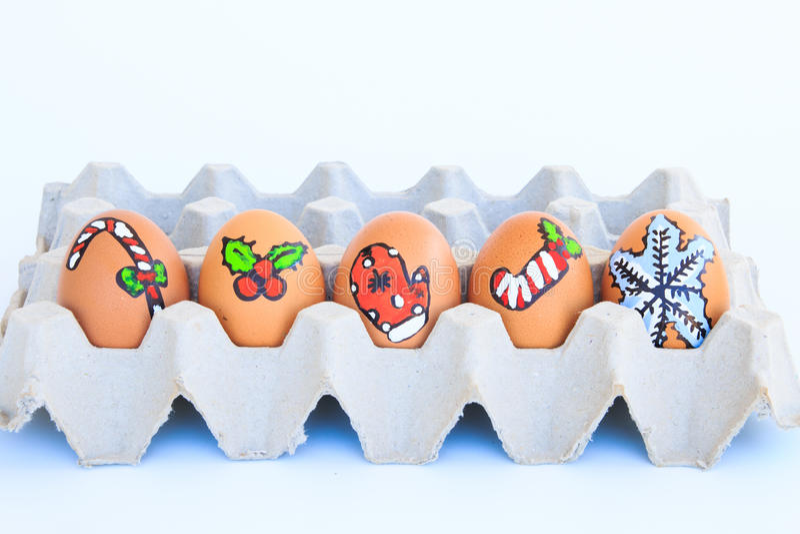 与被画的面孔的圣诞节鸡蛋在纸盒安排了 库存照片