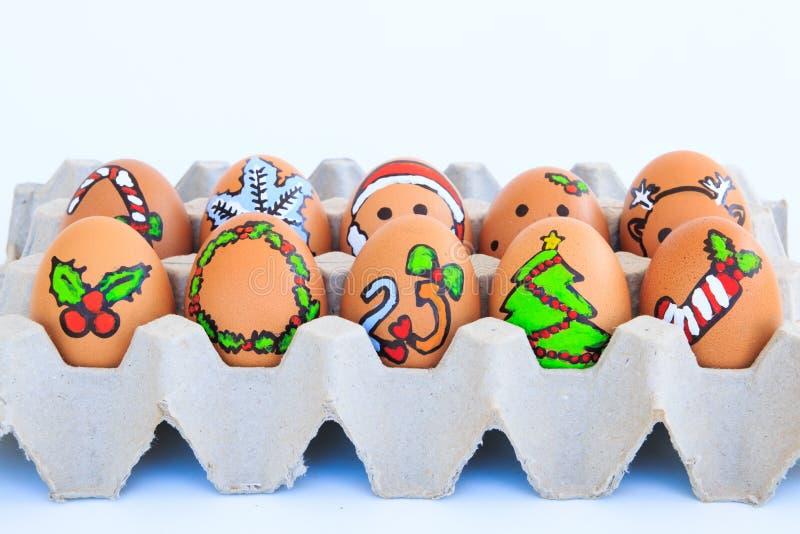 与被画的面孔的圣诞节鸡蛋在纸盒安排了 库存图片