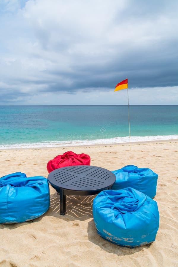 与装豆子小布袋和桌的热带海滩在沙子 免版税库存照片