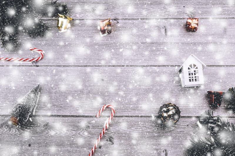 与装饰、礼物盒、树枝和红色中看不中用的物品的圣诞节背景与在木背景的抽象雪 库存图片