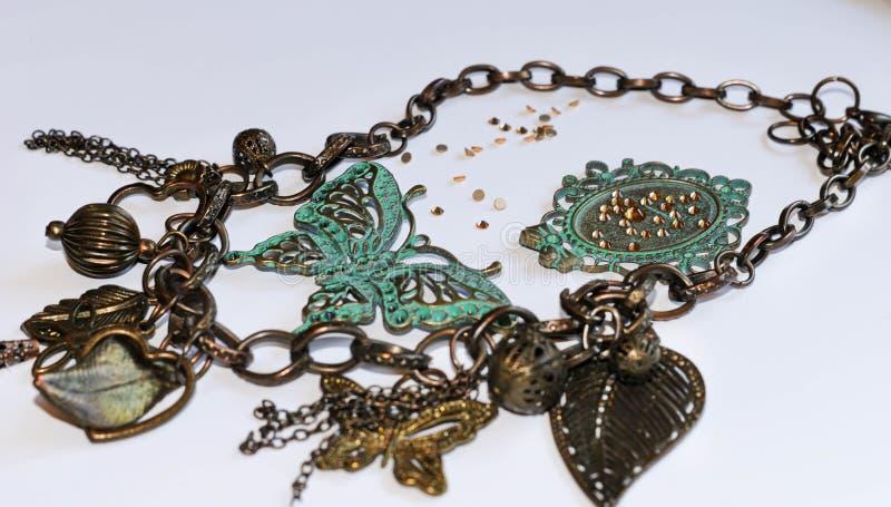 与装饰叶子、小珠、绿色蝴蝶和框架的链子与假钻石 库存照片