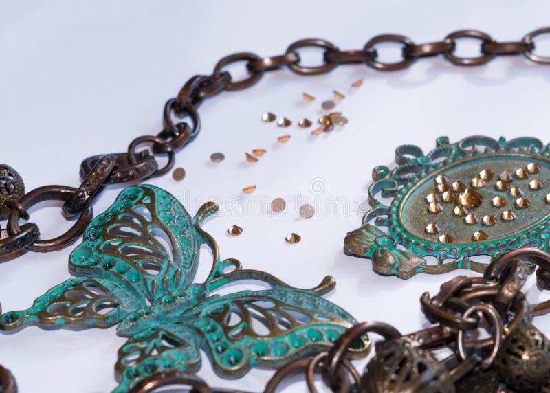 与装饰叶子、小珠、蝴蝶和框架的链子与假钻石 库存照片
