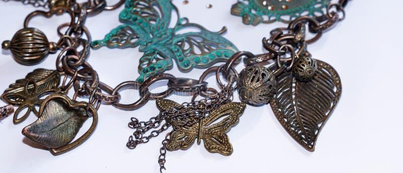 与装饰叶子、小珠、蝴蝶和框架的链子与在白色的假钻石 免版税库存图片