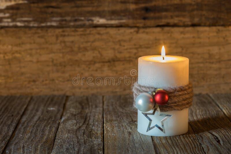 与装饰和木背景的圣诞节蜡烛 免版税库存图片