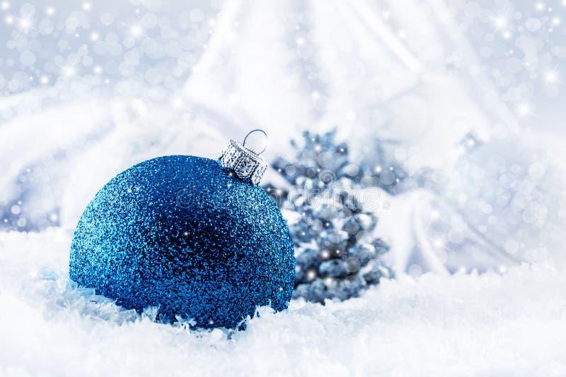 与装饰品的豪华蓝色圣诞节球在圣诞节斯诺伊风景 库存图片